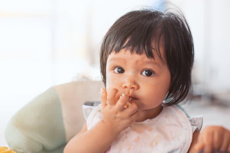 吃健康食品的可爱宝贝亚裔儿童女孩由她自己 免版税库存图片