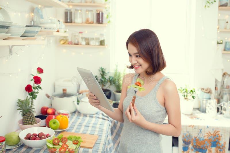 吃健康食物和使用片剂估计的亚裔少妇 库存图片