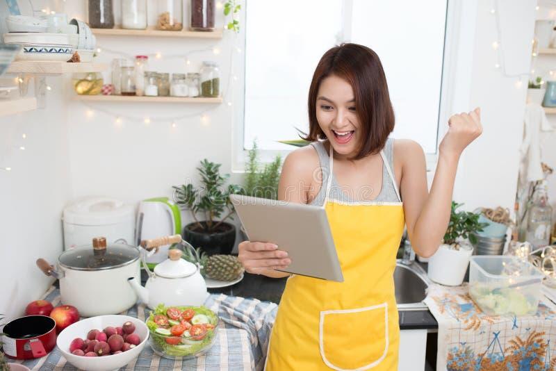 吃健康食物和使用片剂估计的亚裔少妇 图库摄影