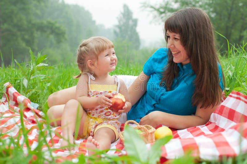 吃健康食物的母亲和女儿 免版税库存图片