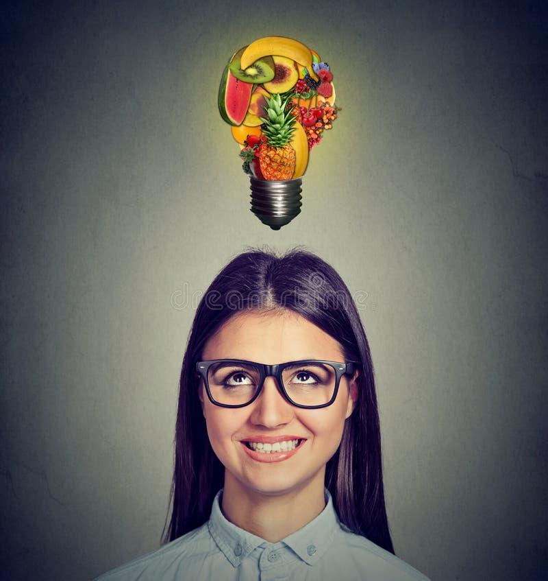 吃健康饮食技巧 看电灯泡的妇女由果子制成 免版税库存照片