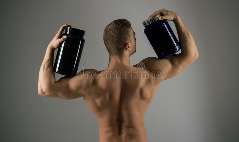 吃健康饮食 坚强男人举行补充瓶 有维生素补充的肌肉人 建身的体育和 库存照片