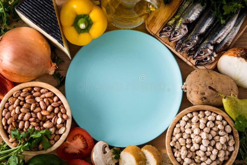 吃健康 地中海的饮食 水果、菜、五谷、胡说的橄榄油和鱼在木桌上 顶视图 免版税库存照片