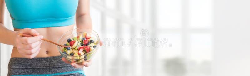吃健康水果沙拉的少妇在锻炼以后 库存照片