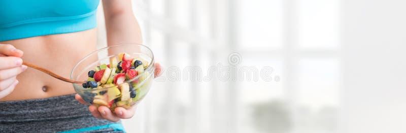 吃健康水果沙拉的少妇在锻炼以后 库存图片