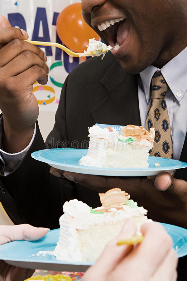 吃党蛋糕的办公室工作者 免版税库存图片