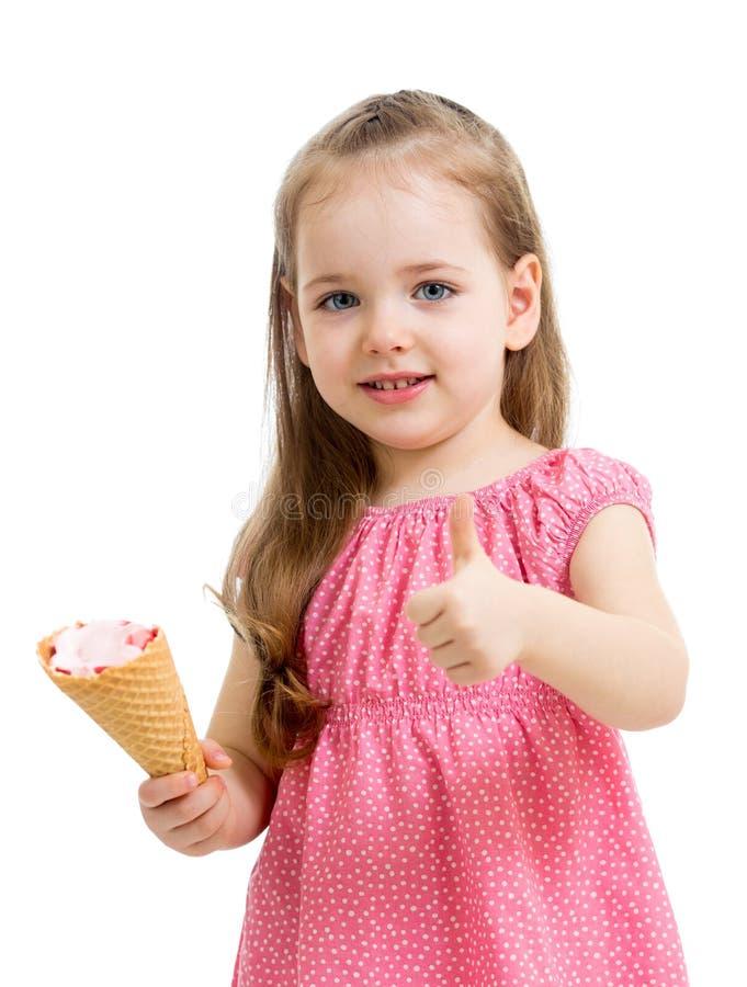 吃冰淇凌和显示赞许的孩子 免版税库存图片