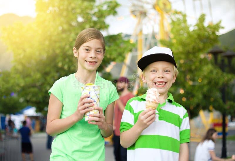 吃冰淇凌和款待的孩子在狂欢节 免版税库存照片