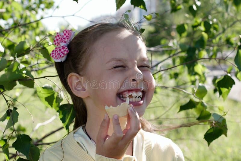 吃冰淇凌和笑的女孩 免版税图库摄影