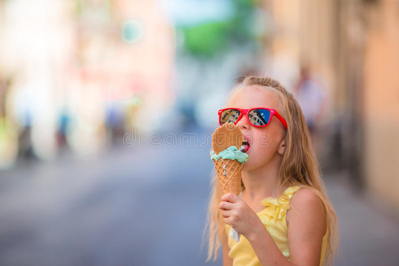 吃冰淇凌的可爱的小女孩户外在夏天 享用真正的意大利gelato的逗人喜爱的孩子在Gelateria附近在罗马 免版税图库摄影