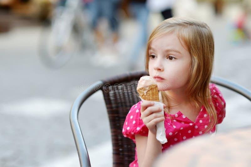 吃冰淇凌的可爱的小女孩户外 免版税库存照片