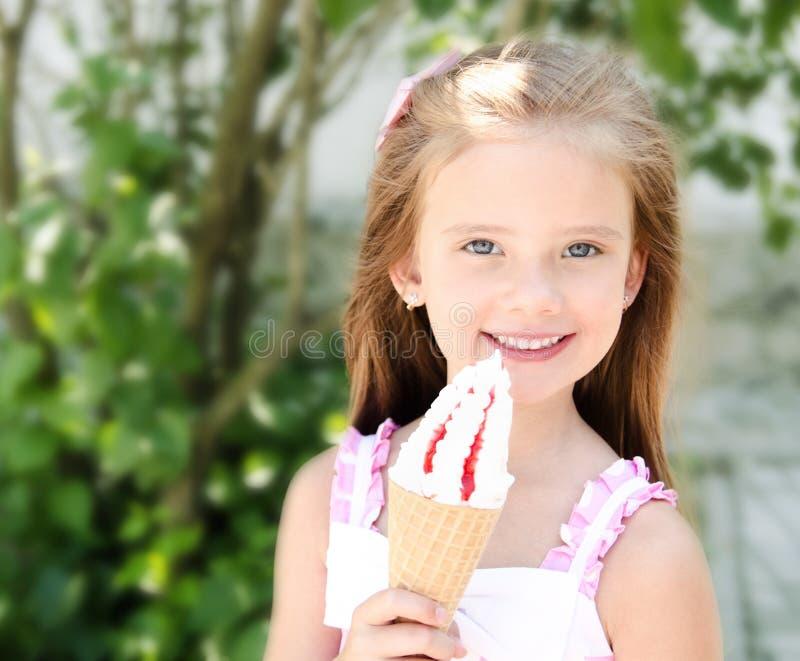 吃冰淇凌的可爱的微笑的小女孩 图库摄影