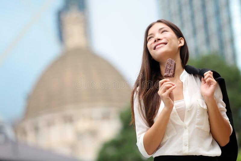 吃冰淇凌的女商人在香港 免版税库存照片