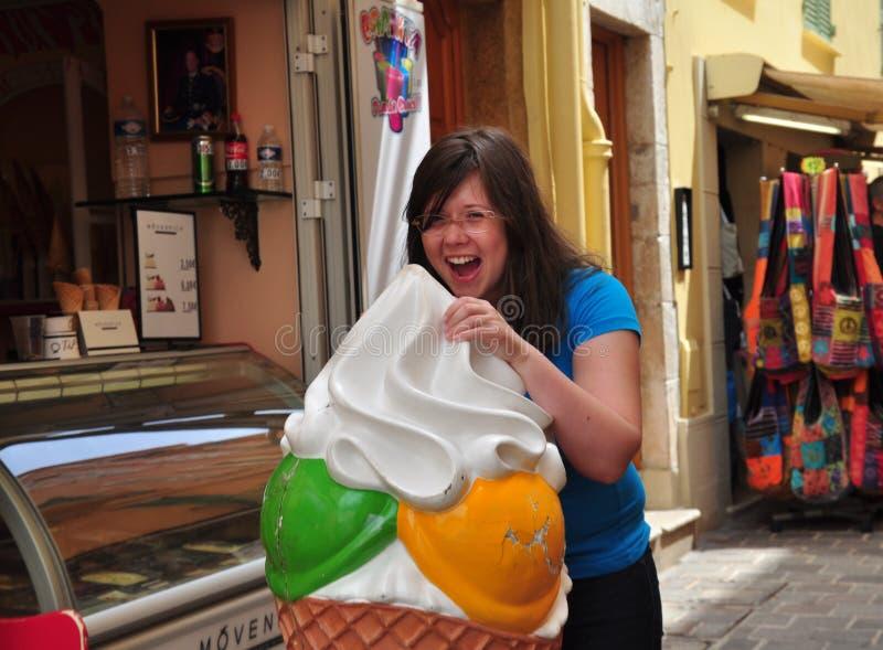 吃冰淇凌的女孩的街道画象 库存图片
