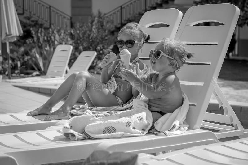 吃冰淇凌的女婴黑白照片在poo附近 库存图片