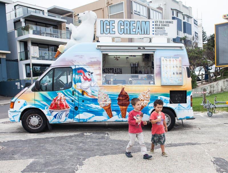 吃冰淇凌的孩子在iceream卡车附近 库存照片