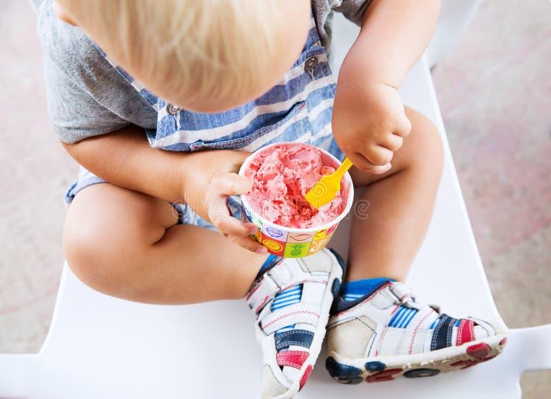 吃冰淇凌的孩子特写镜头细节 图库摄影