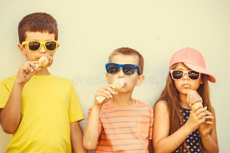 吃冰淇凌的孩子男孩和小女孩 免版税库存照片