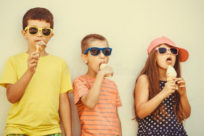 吃冰淇凌的孩子男孩和小女孩 库存图片