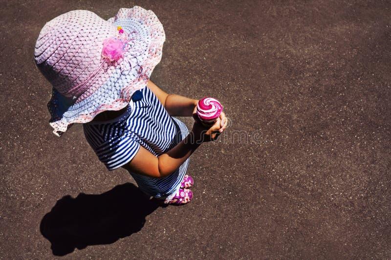 吃冰淇凌的小女孩顶视图 库存图片