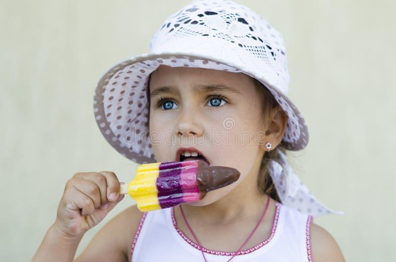 吃冰淇凌的帽子的愉快的女孩 免版税图库摄影