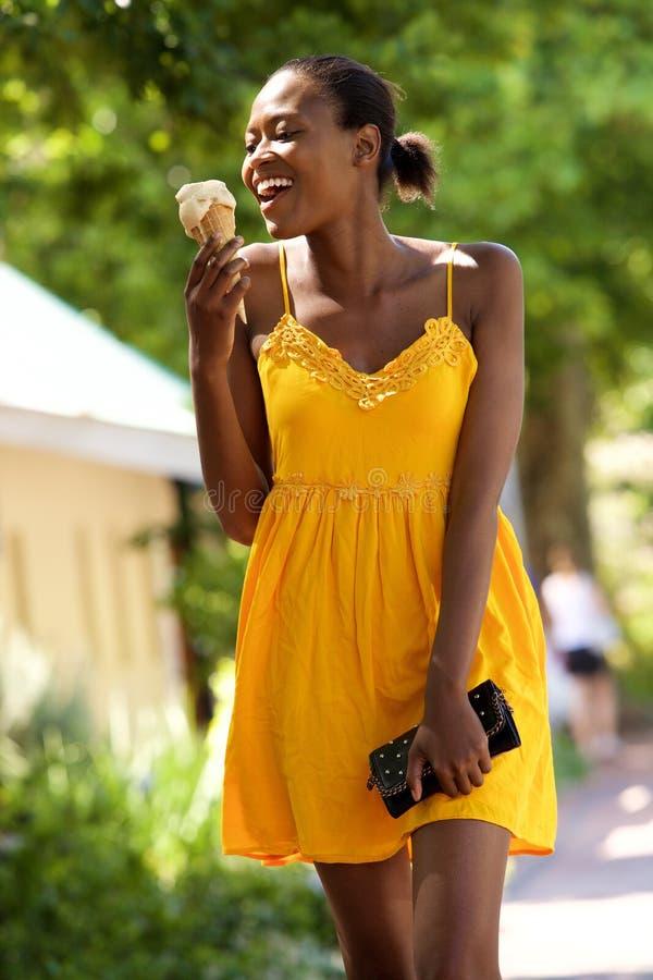 吃冰淇凌的微笑的年轻非洲妇女户外 库存照片