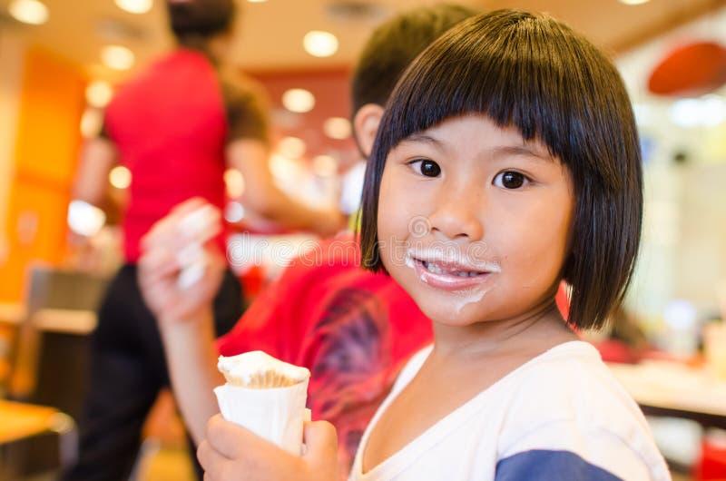 吃冰淇凌的逗人喜爱的亚裔女孩 图库摄影