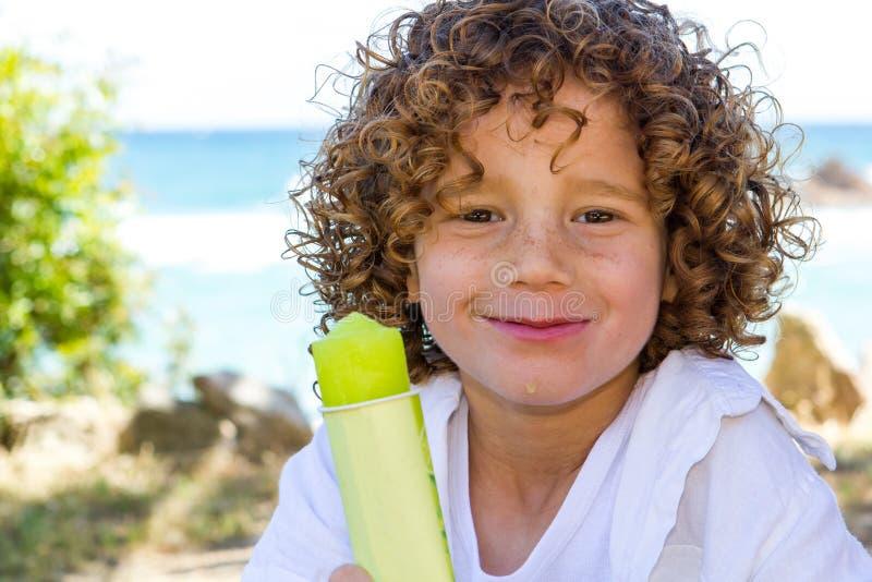 吃冰淇凌的逗人喜爱的男孩。 库存照片