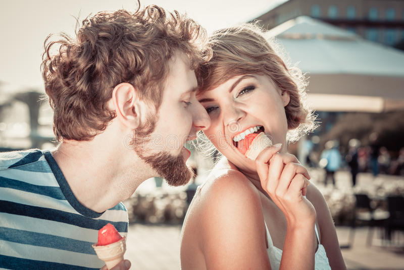 吃冰淇凌的年轻夫妇室外 免版税图库摄影