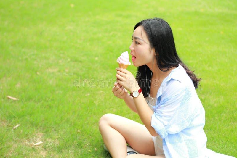 吃冰淇凌的年轻愉快的妇女中国画象  免版税库存图片