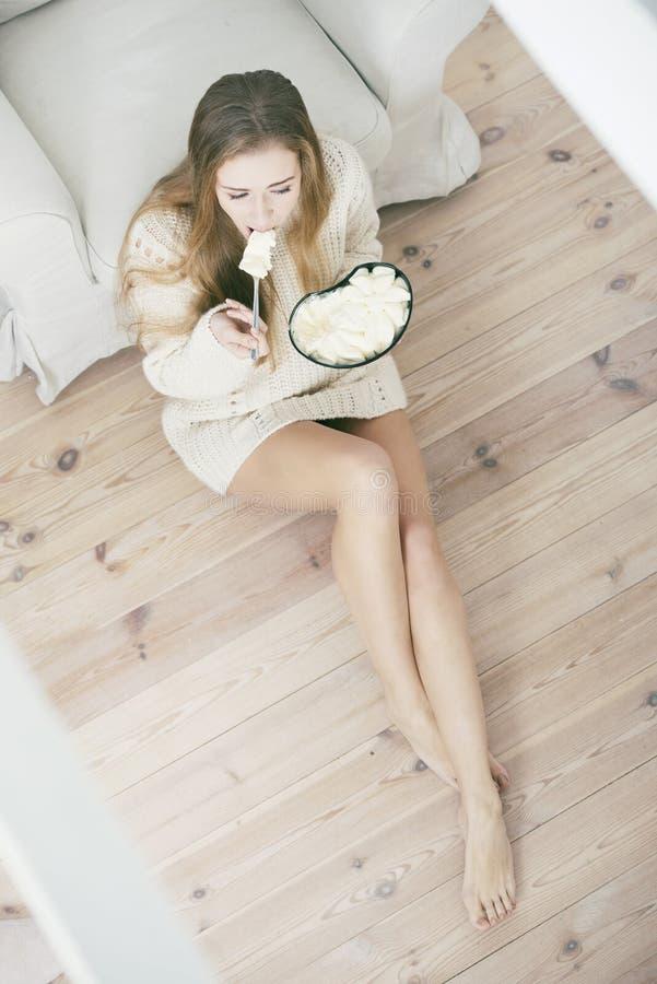吃冰淇凌的年轻沮丧的妇女 免版税库存图片