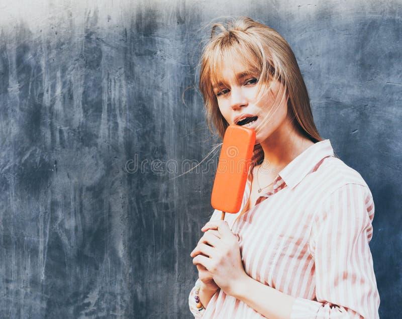 吃冰淇凌的年轻白肤金发的妇女 爱斯基摩-阿留申语 特写镜头 库存照片