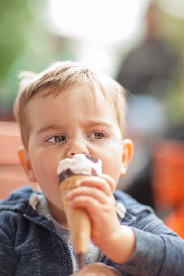 吃冰的小男孩外面在公园在桌上 免版税库存照片
