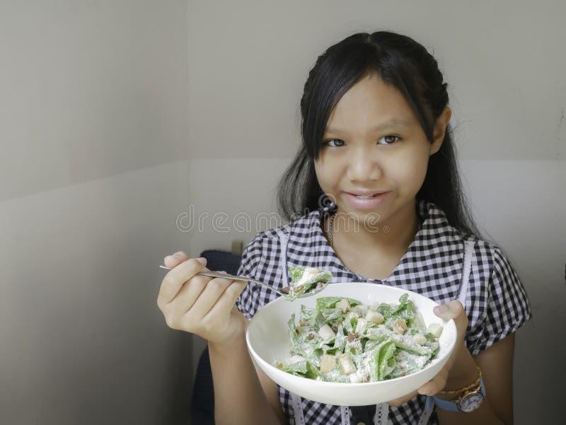 吃凯萨色拉的女孩 免版税库存图片