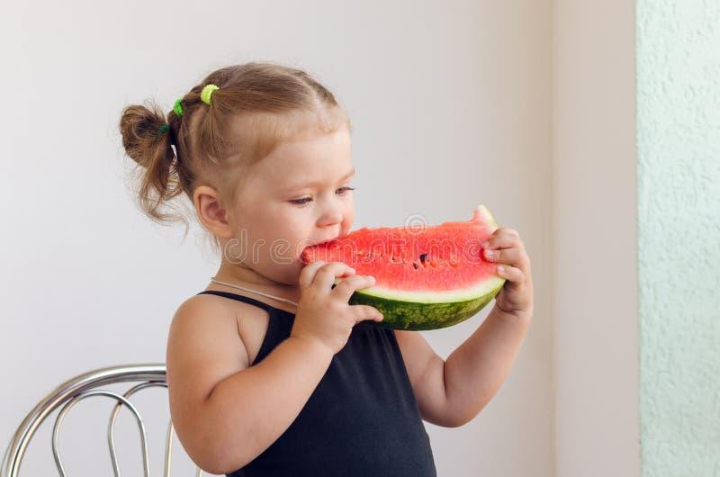 吃切片水多的成熟西瓜的女孩的画象 免版税库存照片