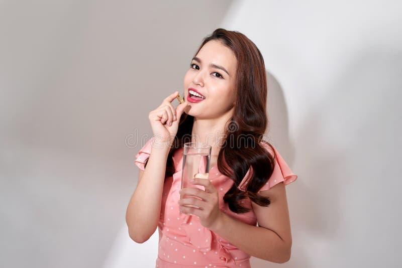 吃医疗保健的美丽的亚裔妇女维生素药片在hom 库存照片