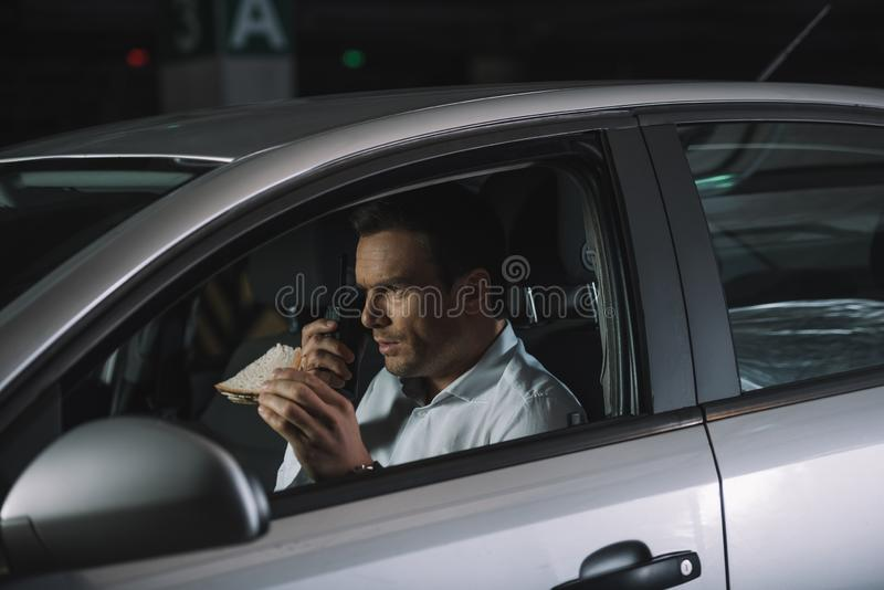 吃午餐和使用有声电影walkie的男性私家侦探 免版税图库摄影