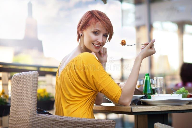 吃午餐微笑的妇女 图库摄影