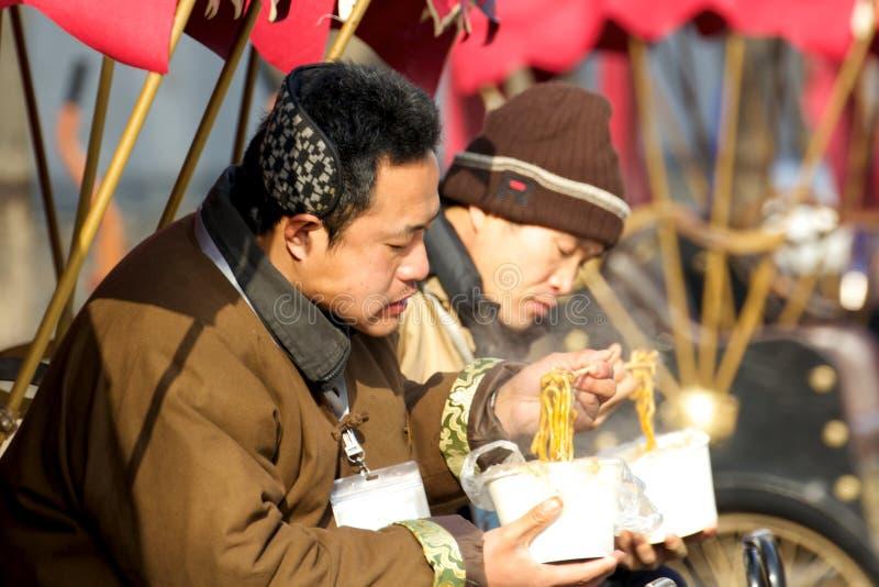 吃午餐的人力车司机方便面在北京,中国一个旅游胜地的冬天  免版税图库摄影