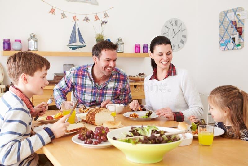 吃午餐的家庭在厨房用桌上 库存照片