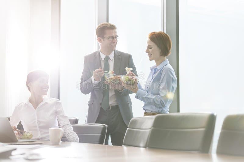吃午餐的微笑的企业同事在会议室里在见面期间在办公室 免版税图库摄影