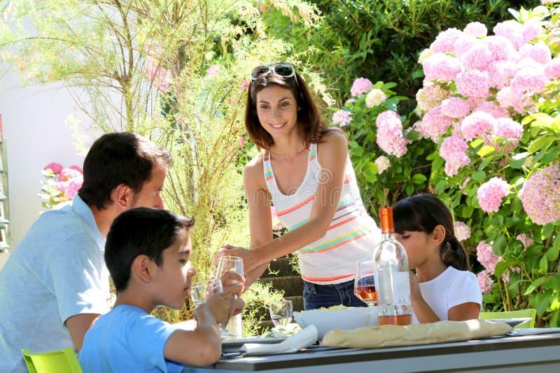 吃午餐的愉快的家庭在大阳台庭院里 免版税库存照片