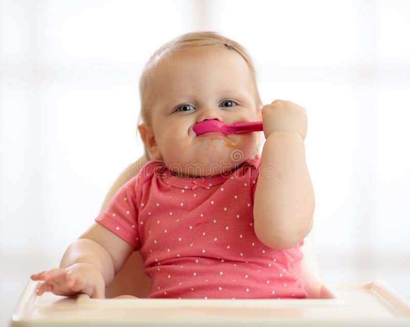 吃单独食物的微笑的滑稽的婴孩 库存图片