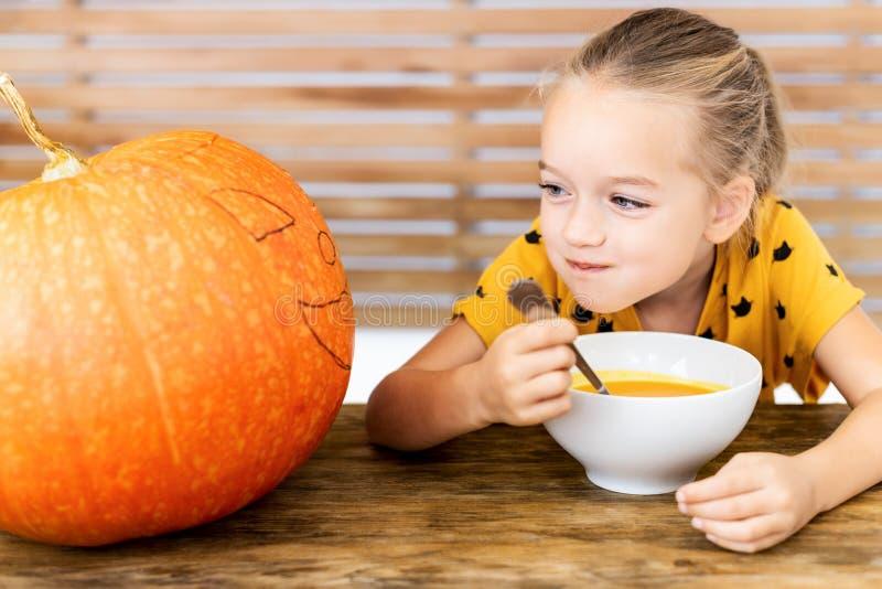 吃南瓜汤和看一个大万圣夜南瓜,与狠毒面孔表示的逗人喜爱的小女孩 万圣节 免版税库存照片