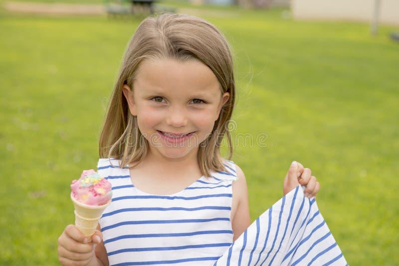 吃可口冰淇凌微笑的可爱和美好的白肤金发的女孩6或7岁愉快在绿草领域ba 库存图片