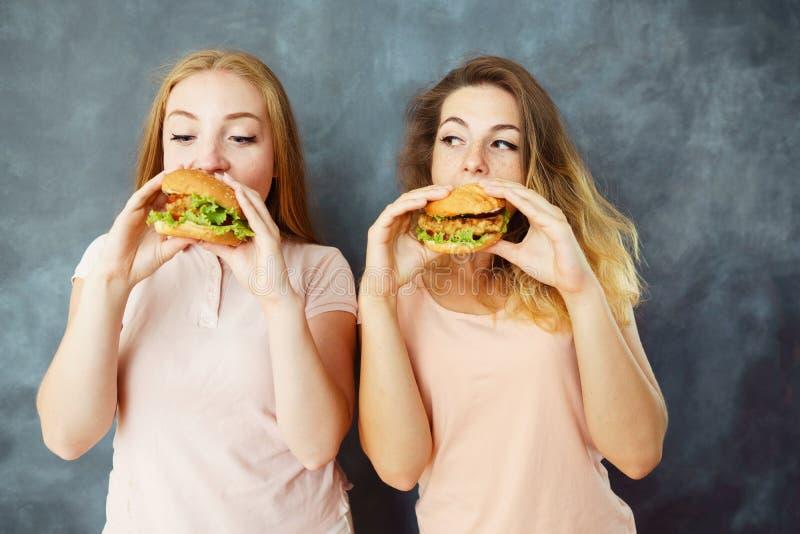 吃可口汉堡的两个逗人喜爱的少妇 免版税库存照片
