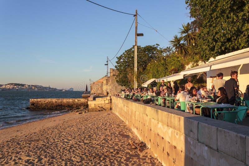 吃和喝在室外餐馆大阳台的游人在河沿 免版税库存照片