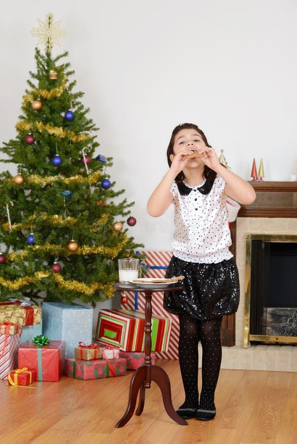 吃圣诞老人曲奇饼的小女孩 库存照片