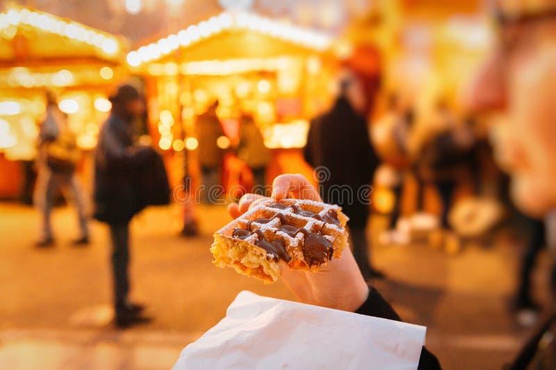 吃圣诞节传统奶蛋烘饼的妇女在圣诞节市场上 免版税库存图片