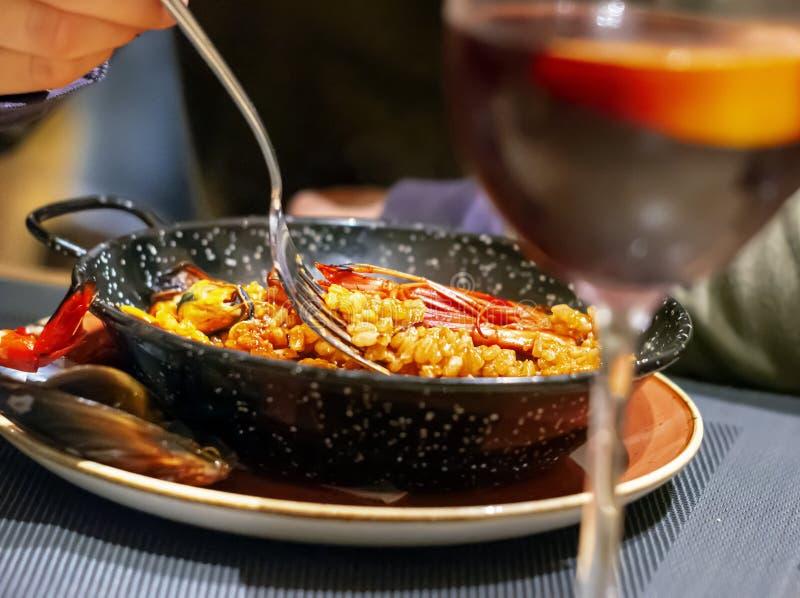 吃在一个黑平底锅的瓦伦西亚语肉菜饭使用叉子 免版税库存照片